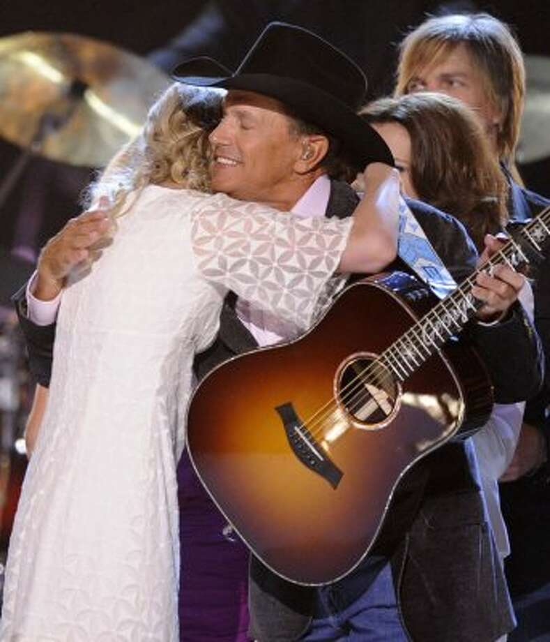 Taylor Swift, left, hugs  George Strait during the finale of the ACM Artist of the Decade All Star Concert on Monday, April 6, 2009, in Las Vegas. George Strait is the recipient of the Artist of the Decade award.
