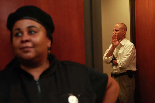Krystal Muhammad of the New Black United Front next to security officer at Harris County District Attorney Pat Lykos' office Friday, May 18, 2012. (Johnny Hanson / Chronicle)