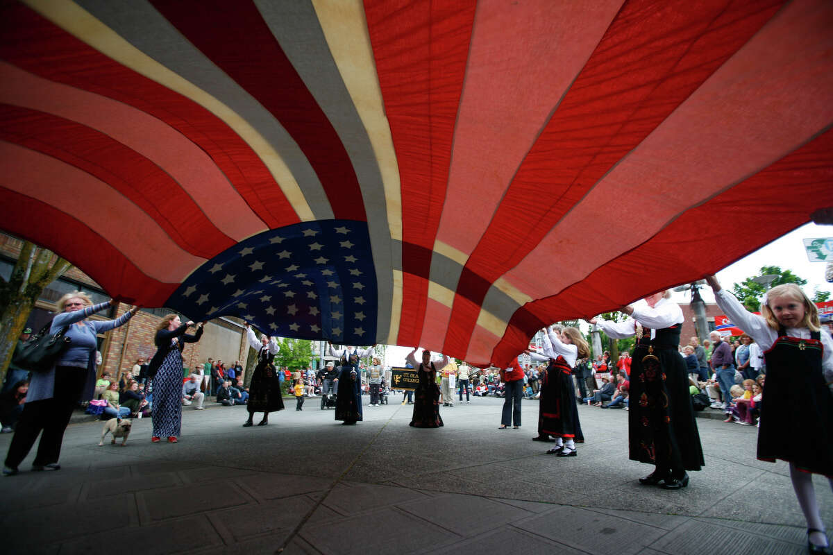A group of parade participants hold up a large American flag during the Syttende Mai Parade in Ballard.