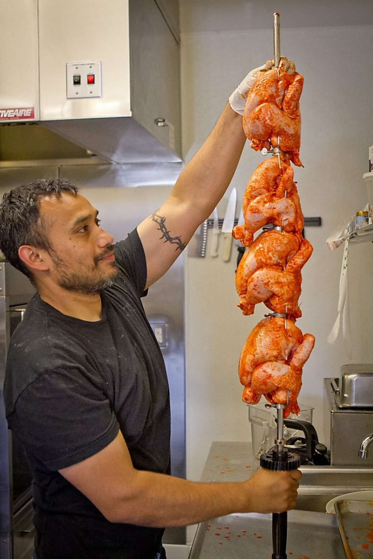 Chef Gilberth Cab slides chickens onto the rotisserie skewer at Gilberth's Restaurant in San Francisco , Calif., on Saturday, May 5th, 2012.