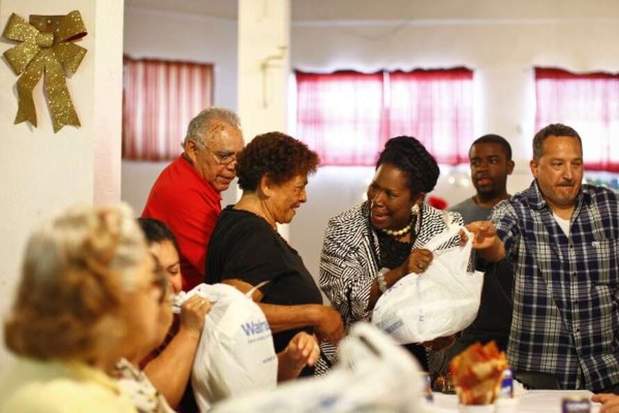 U.S. Congresswoman Sheila Jackson Lee helps distribute a turkey to Delfina Martinez as Joe Perez loo