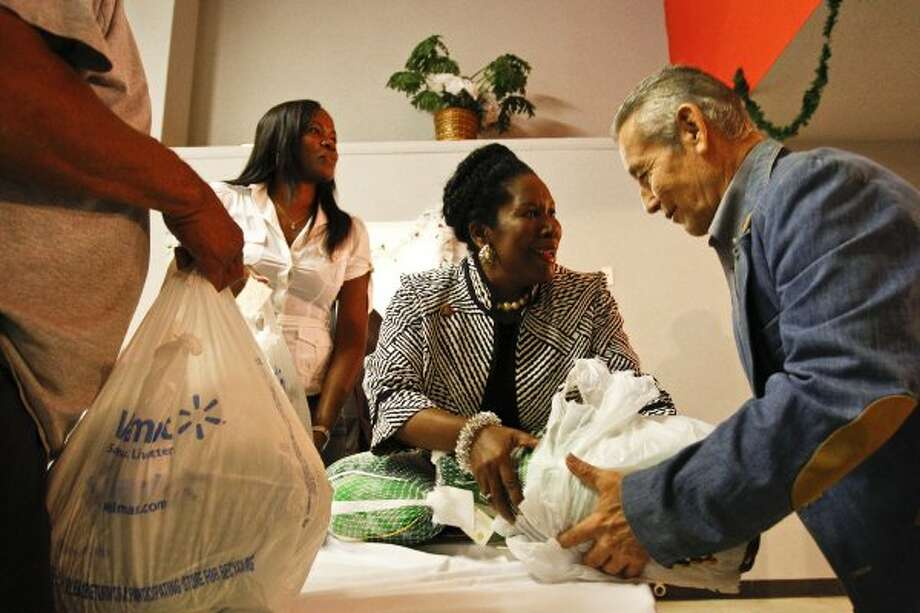 Former basketball star Sheryl Swoopes and Sheila Jackson Lee help distribute a turkey to Jose Montalvo at the Latino Learning Center during the 16th annual turkey giveaway Tuesday, Nov. 23, 2010, in Houston. (Michael Paulsen / Houston Chronicle)