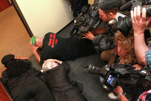 The media bear down on the protesters on the floor of the Harris County District Attorney's Office before their arrest Friday, May 18, 2012. (Johnny Hanson / Chronicle)