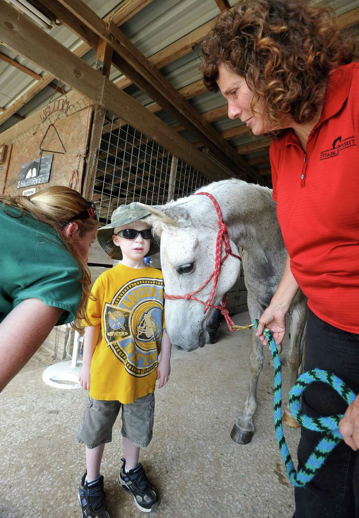 Stable Spirits helps people with mental health problems and others who may need physical therapy, recover through working with horses. Volunteers Rebekah Schaper left, works with Executive Director Katie Durio, right, getting Cash Huebel, middle, 5, ready to partake in the
