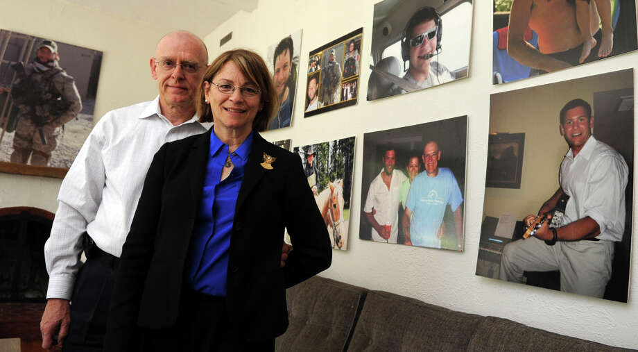 Pat and Michael Parry, parents of Navy SEAL Brian Bill, pose for a photo in a room decorated with large photos of Bill in their home in Stamford on Friday, May 18, 2012. Photo: Lindsay Niegelberg / Stamford Advocate
