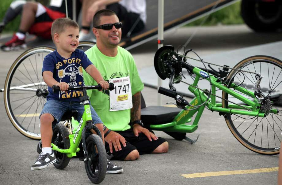 Three year old Seth Breece, left, poses with his Father Jeremy Breece at the start of the Center for the Intrepid Mini Try.  More than 100 wounded service members took their rehabilitation to the next level in the Center for the Intrepid Mini Try at Joint Base San Antonio Post Fort Sam Houston Outdoor Aquatic Center and track. Friday, May 18, 2012. The 5th annual Mini-Try consisted of a 10-mile bicycle ride, 500-meter swim, and a 2-mile run/walk.  Photo/Bob Owen Photo: BOB OWEN, San Antonio Express-News / © 2012 San Antonio Express-News