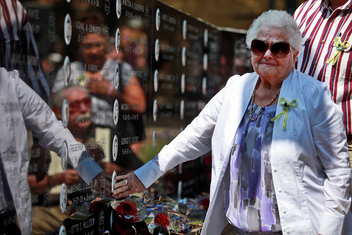 Arleta Spannagel touches the picture of her son, Patrolman Russell D. Spannagel, who was killed in 1973 at the age of 24, on the memorial wall after