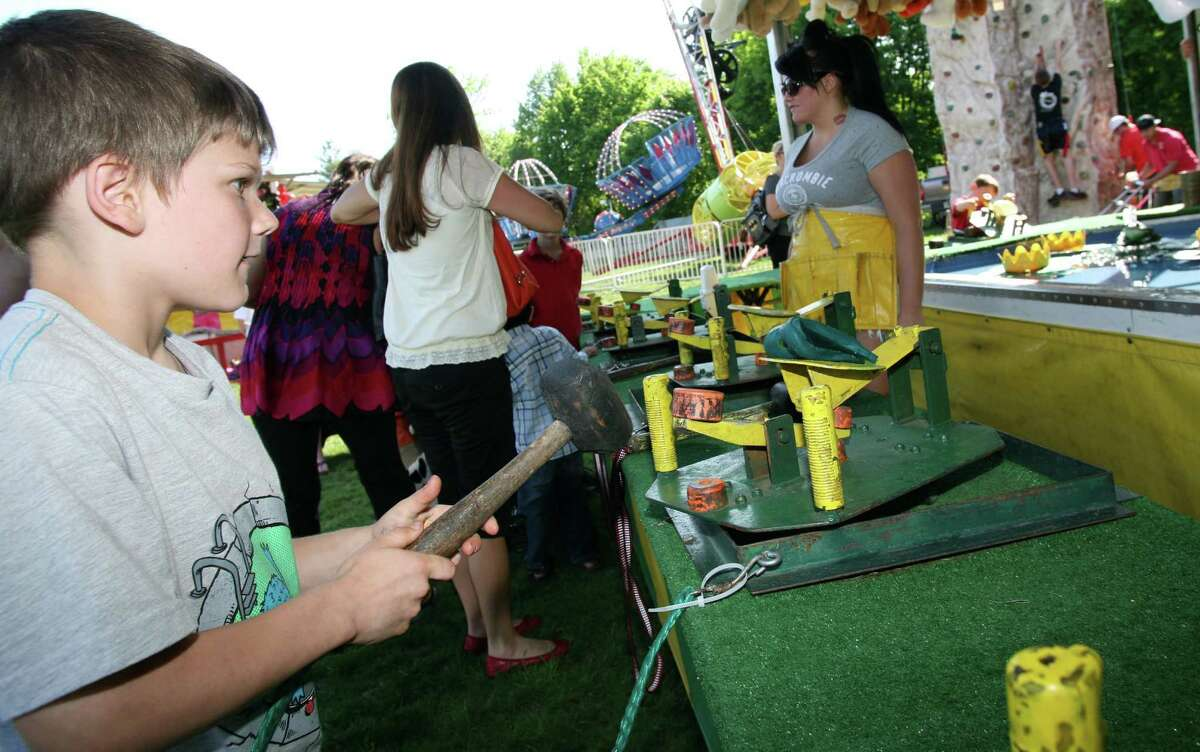 Jake Shreders lines up his shot at the Frog Bog game during the first day of the Cos Cob School's May Fair Friday, May 19, 2012.
