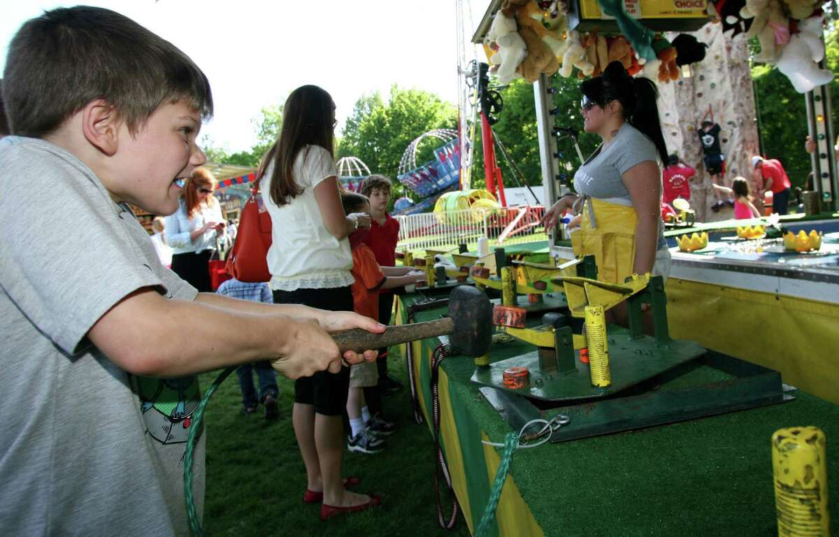 Jake Shreders puts the hammer down at the Frog Bog game during the first day of the Cos Cob School's May Fair Friday, May 18, 2012.