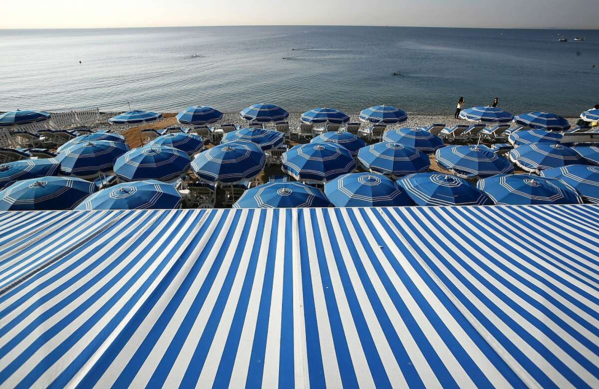 FILE - In this file photo taken Sept. 27, 2011, people swim in the Mediterranean Sea as blue beach umbrellas provide shade from the sun along the beach in Nice, southeastern France. The city of Nice attracts tourists year-round thanks to the flower market, restaurants, historic sites and events ranging from Mardi Gras to the annual film festival in Cannes. (AP Photo/Lionel Cironneau, File)