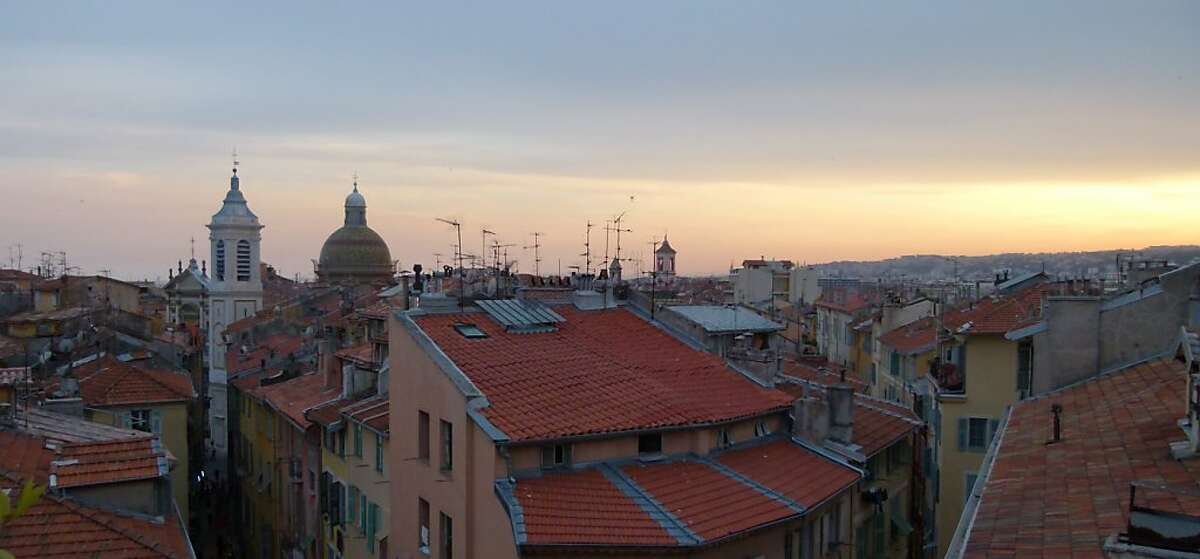 """This photo taken May 2011 shows the rooftops of Old Nice at sunset in Nice, France. The picturesque setting of the Riviera has been the backdrop for a number of movies including """"To Catch a Thief"""" starring Cary Grant and Grace Kelly. The city of Nice attracts tourists year-round thanks to the flower markets, restaurants, historic sites and events ranging from Mardi Gras to the annual film festival in Cannes. (AP Photos/Michelle Locke)"""