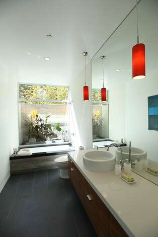 Pendant lighting showcases the modern fixtures in the lower-level bath. Photo: Sean McCardle