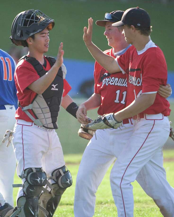 Greenwich's Ricky Okazaki, left, and Nick Bancroft, right, exchange high fives while Max Barefoot is in the middle after the Cardinals completed an undefeated regular season by beating Danbury, 2-1, Friday at Danbury High School. Photo: Barry Horn / The News-Times Freelance