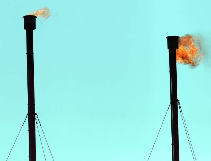 Flares burn under the Texas sky near petroleum and gas storage tanks in McMullen County, Texas. The