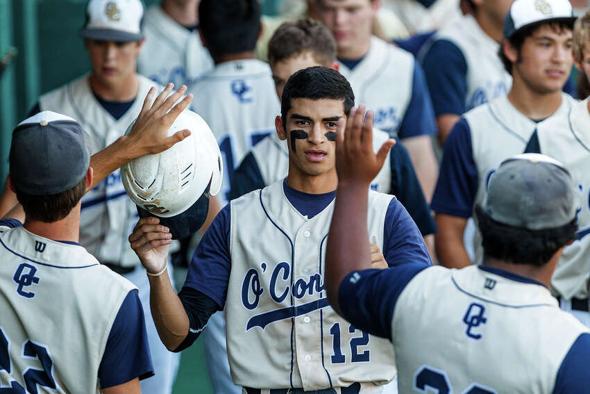 O'Connor's Roy Gonzales (center) is greeted by teammates in the duggout after scoring a run in the seventh inning during the opener of the Panther's best-of-3 third round series with Churchill at Nelson Wolff Stadium on May 18, 2012. O'Connor held the Chargers to two hits and came away with a 3-1 victory. MARVIN PFEIFFER/ mpfeiffer@express-news.net