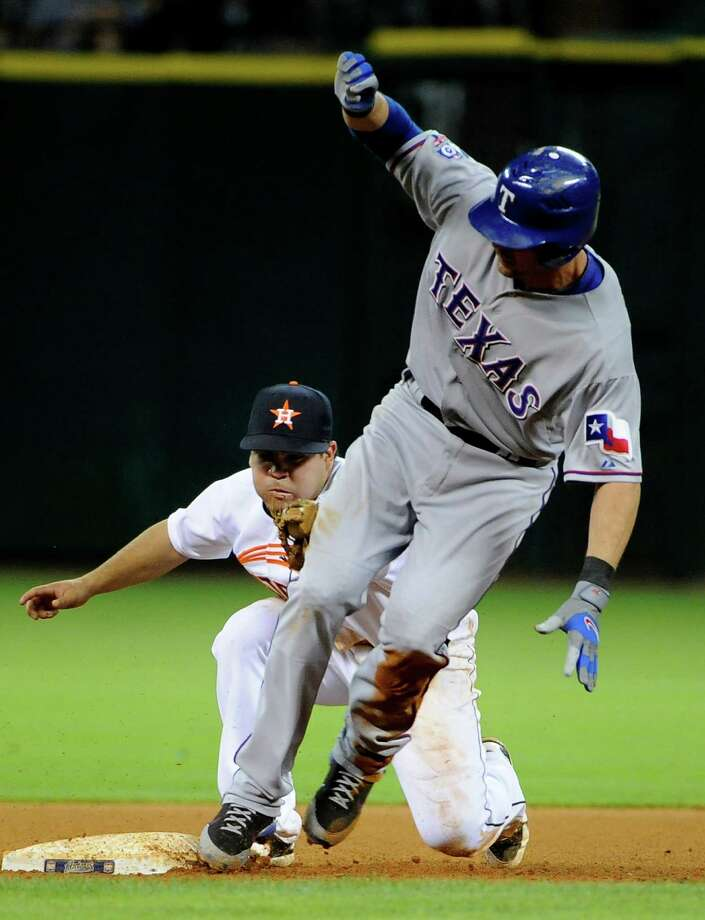 Houston Astros' Jose Altuve, left, is late with the tag and Texas Rangers' Michael Young, right, is safe at second base for an RBI double in the fifth inning of a baseball game, Friday, May 18, 2012, in Houston. Photo: AP
