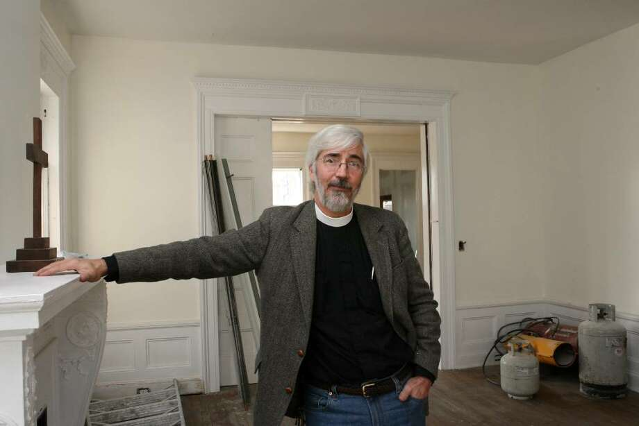 The Rev. Dr. Geoffrey Hahneman stands in an almost finished former St Johns rectory building    on Fairfield Avenue in Bridgeport on Saturday, Nov. 21, 2009. He was instrumental in saving it from demolition. Hundreds of volunteers have rescued it and have been rehabbing the building for over 3 years. The city  taxed the building during its renovation, which left the church with over 50,000 lien. The building will be used for a family center, a clothes closet, a pantry and an office space. Photo: B.K. Angeletti / Connecticut Post