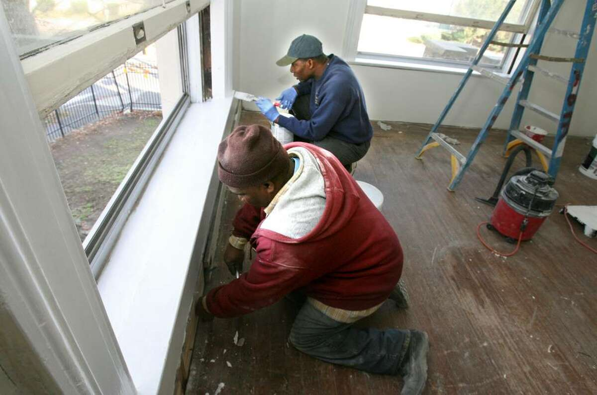 Volunteers , Douglas Graham, left, and Raymond Panther, work on Saturday, Nov. 21, 2009 in an upstairs room in the St John's former rectory building on Fairfield Avenue in Bridgeport. The building was on the brink of demolition but hundreds of volunteers have rescued it and have been rehabbing the building for over 3 years. The city taxed the building during its renovation, which left the church with over 50,000 lien. The building will be used for a family center, a clothes closet, a pantry and an office space.