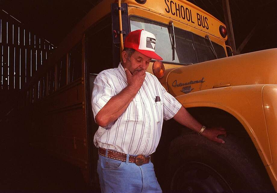 File - In this 1992 file photo, Frank Edward Ray stands in Chowchilla, Calif., by the bus from which he and 26 students were kidnapped. Ray, the school bus driver hailed as a hero for helping 26 students escape after three men kidnapped the group and buried the entire bus underground in 1976 has died. He was 91. (AP Photo/Merced Sun Star, File) Photo: Associated Press