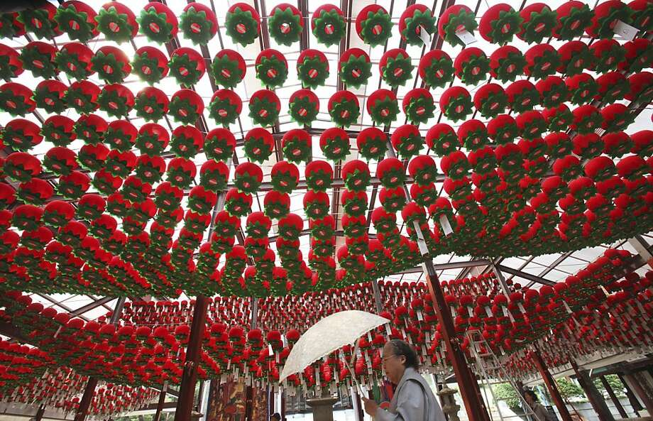 A South Korean Buddhist walks under lanterns to celebrate the upcoming Buddha's Birthday on May 28 at the Bong Eun temple in Seoul, South Korea, Friday, May 18, 2012. (AP Photo/Ahn Young-joon) Photo: Ahn Young-joon, Associated Press