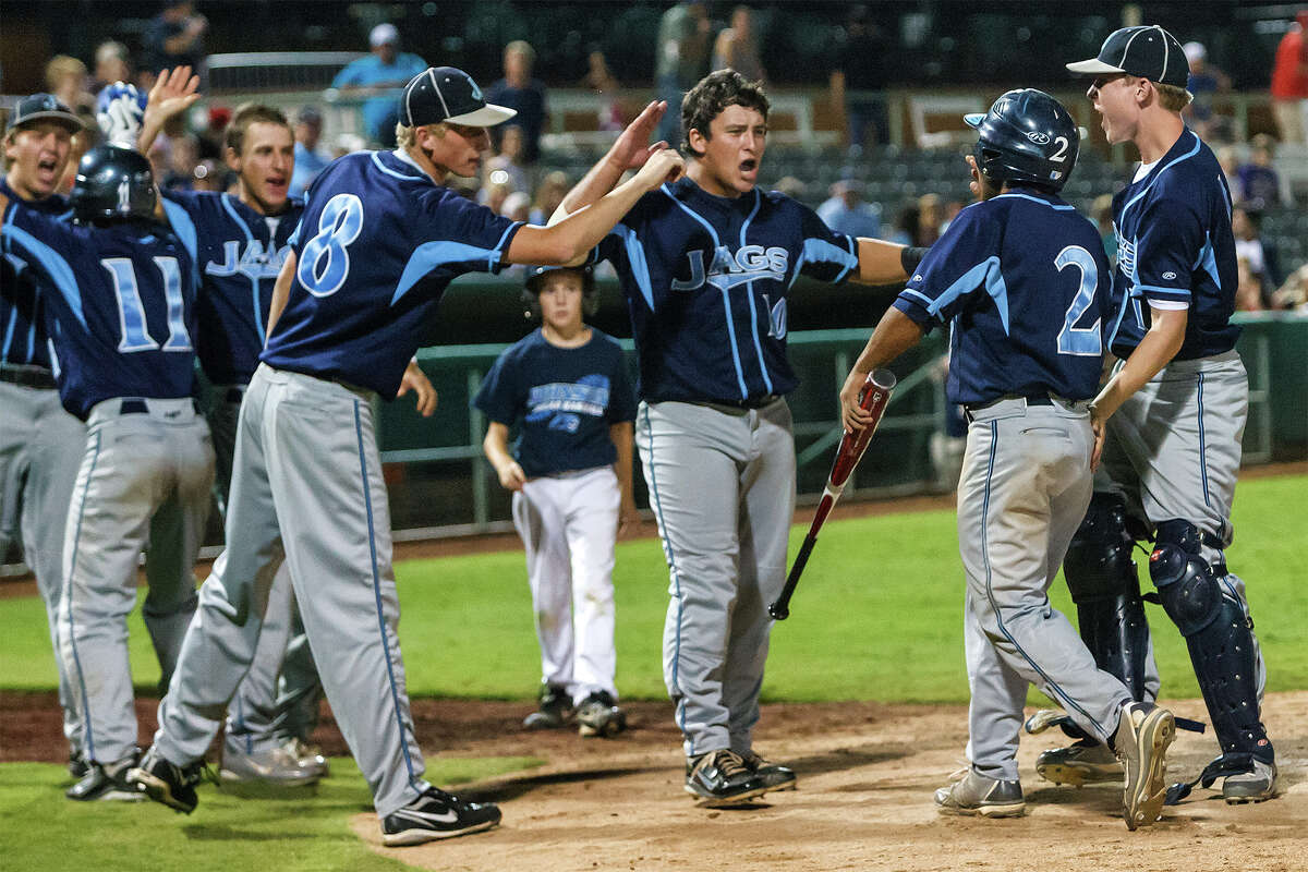 The Johnson Jaguars pour out of the dugout to congratulate Joseph Collazo (second from right) after he scored the tying run in the bottom of the sixth inning against Corpus Christi Carroll in the opener of the their third round series at Nelson Wolff Stadium on May 18, 2012. Johnson won the game 3-2 . MARVIN PFEIFFER/ mpfeiffer@express-news.net