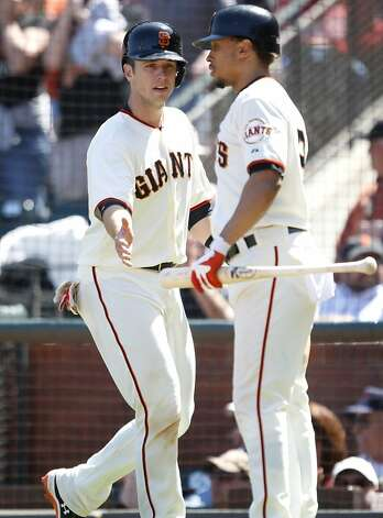 The Giants' Buster Posey, left, gets congratulated by Emmanuel Burriss after scoring off a hit by Brandon Belt in the seventh inning of their game against the Cardinals in San Francisco, Calif., Thursday, May 17, 2012.  The Giants won 7-5. Photo: Sarah Rice, Special To The Chronicle