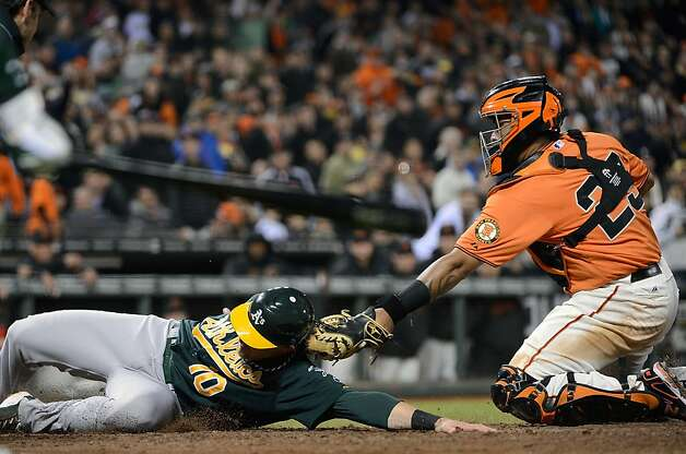 SAN FRANCISCO, CA - MAY 18:  Daric Barton #10 of the Oakland Athletics scores on an RBI double from Josh Donaldson #20, sliding around the tag of Hector Sanchez #29 of the San Francisco Giants in the fifth inning at AT&T Park on May 18, 2012 in San Francisco, California.  (Photo by Thearon W. Henderson/Getty Images) Photo: Thearon W. Henderson, Getty Images