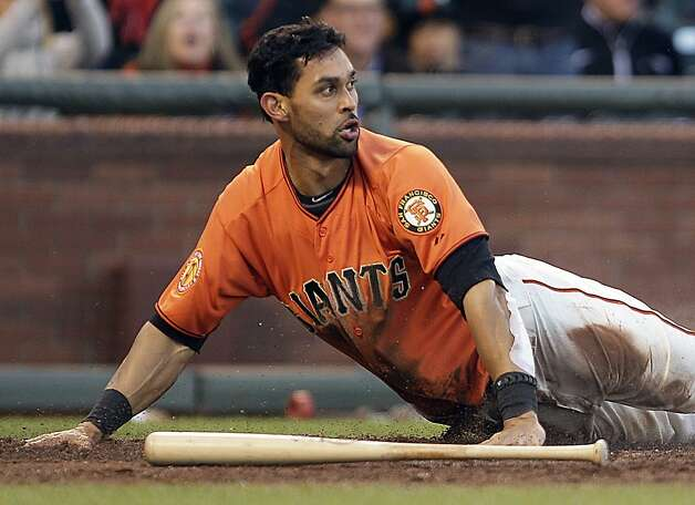 San Francisco Giants' Angel Pagan turns to check the call after sliding to score against the Oakland Athletics during the second inning of a baseball game Friday, May 18, 2012, in San Francisco. (AP Photo/Ben Margot) Photo: Ben Margot, Associated Press