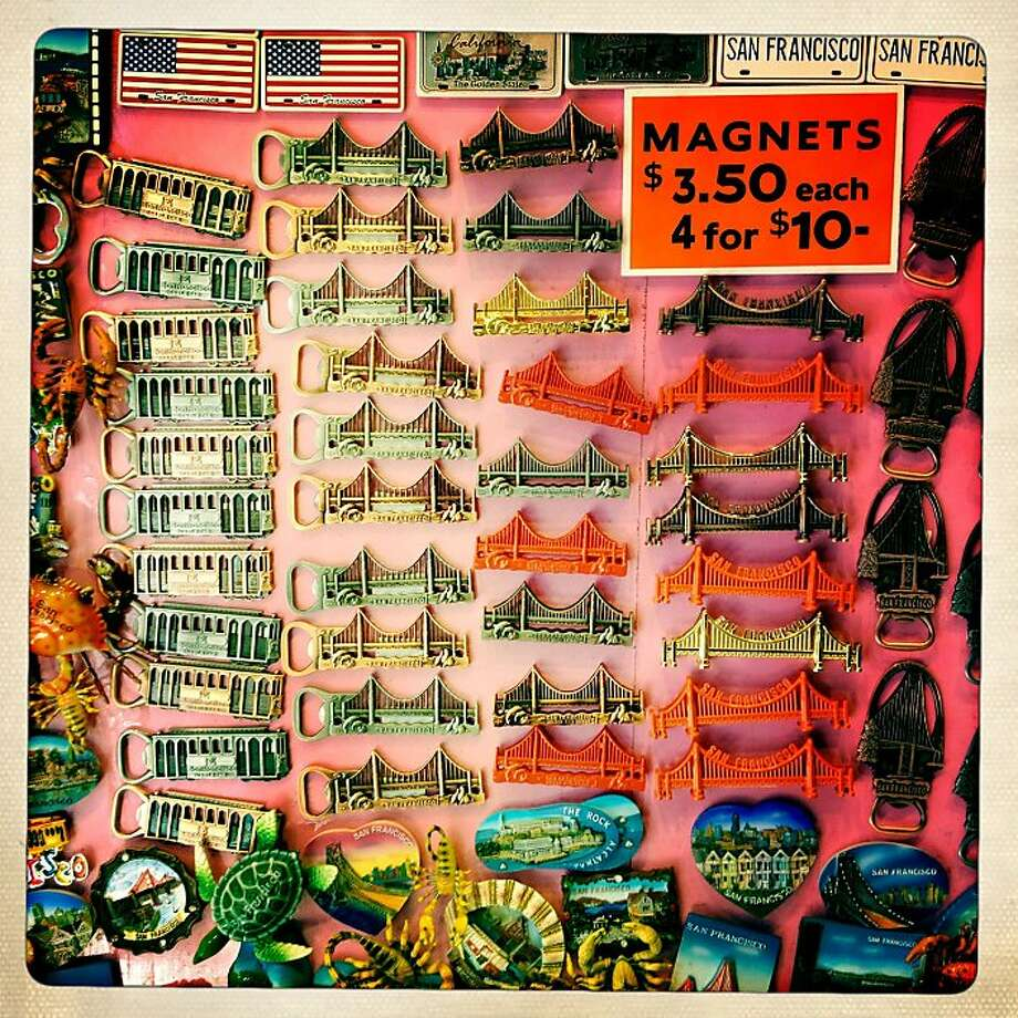 "Golden Gate Bridge magnets, 4 for $10, at Digital Photo Center on Grant Avenue in San Francisco, Calif. -  In the 75 yeas since it completion the Golden Gate Bridge has become an icon to the world. For the San Francisco bay area businesses it has come to represent an undeniable marketing strategy. Images of orange towers grace beer cans and billboards. The simple words ""golden"" and ""gate"" precede more than a few store front signs. The power of the bridge is undeniable. Photo: Mike Kepka, The Chronicle"