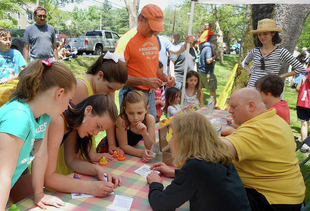 Adults and kids register their race ducks for the Duckie Derby in the Mill River on Saturday. Photo: Mike Lauterborn / Fairfield Citizen contributed