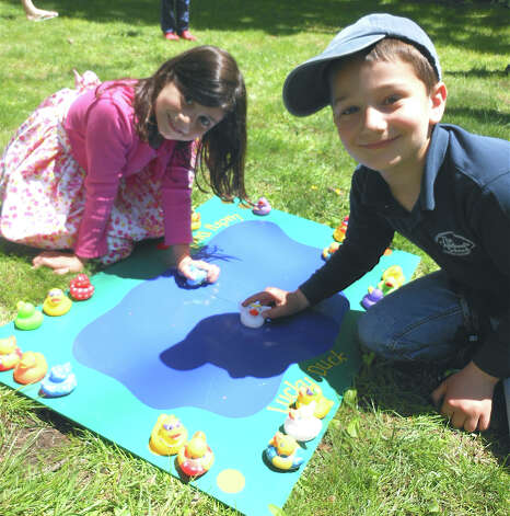 Rose and Michael Cairo, ages 5 and 6, respectively, play a Lucky Duck board game at the Duckie Derby on Saturday. Photo: Mike Lauterborn / Fairfield Citizen contributed