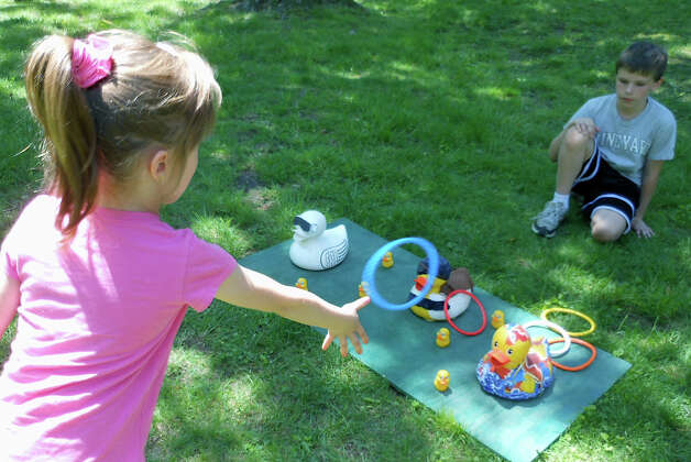 Noemi Farkas, 5, of Fairfield, tries her hand at duck ring toss Saturday at the Duckie Derby benefiting St. Catherine's Academy. Photo: Mike Lauterborn / Fairfield Citizen contributed