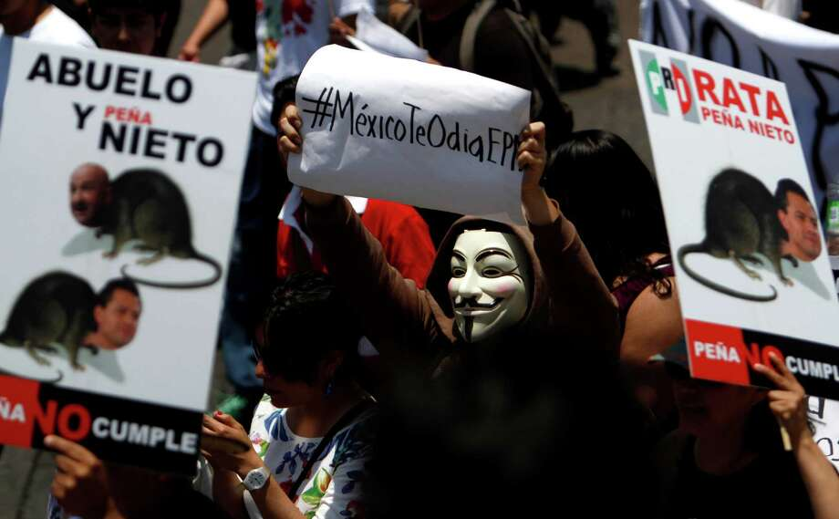"A man wearing a Guy Fawkes mask holds up a sign that reads in Spanish: ""#Mexico hates you, EPN or Enrique Pena Nieto,"" during a demonstration where thousands of college-age students marched down Mexico City's main boulevard to protest a possible return of the old ruling Institutional Revolutionary Party, PRI, Saturday, May 19, 2012. PRI presidential candidate Enrique Pena Nieto leads in polls ahead of the July 1 elections. Photo: Marco Ugarte"