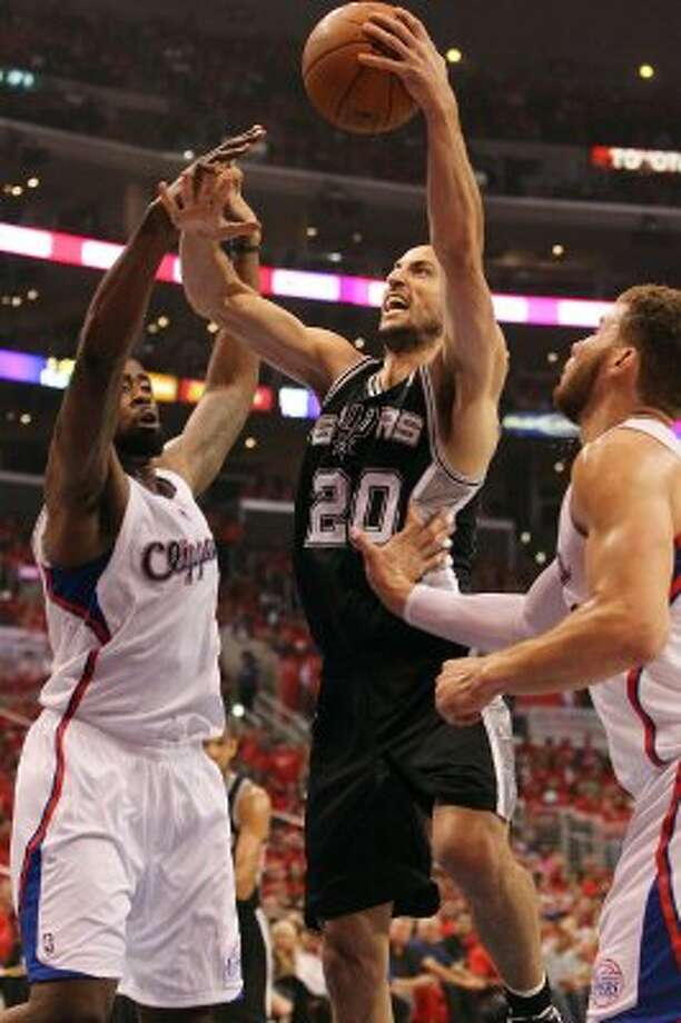 Spurs' Manu Ginobili (20) takes a hard shot against the Los Angeles Clippers' DeAndre Jordan (06) and Blake Griffin (32) in the first half of game three of the Western Conference semifinals at the Staples Center in Los Angeles on Saturday, May 19, 2012.   Kin Man Hui/Express-News (Kin Man Hui / SAN ANTONIO EXPRESS-NEWS)