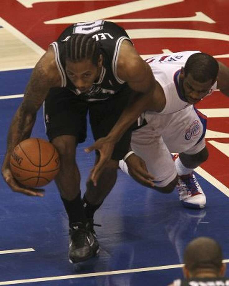 San Antonio Spurs Kawhi Leonard (02) grabs the loose ball after a scramble with Los Angeles Clippers Chris Paul (03) during the first half of game three of the Western Conference semifinals at Staples Center in Los Angeles, Saturday, May 19, 2012.  Jerry Lara/San Antonio Express-News (Jerry Lara / San Antonio Express-News)