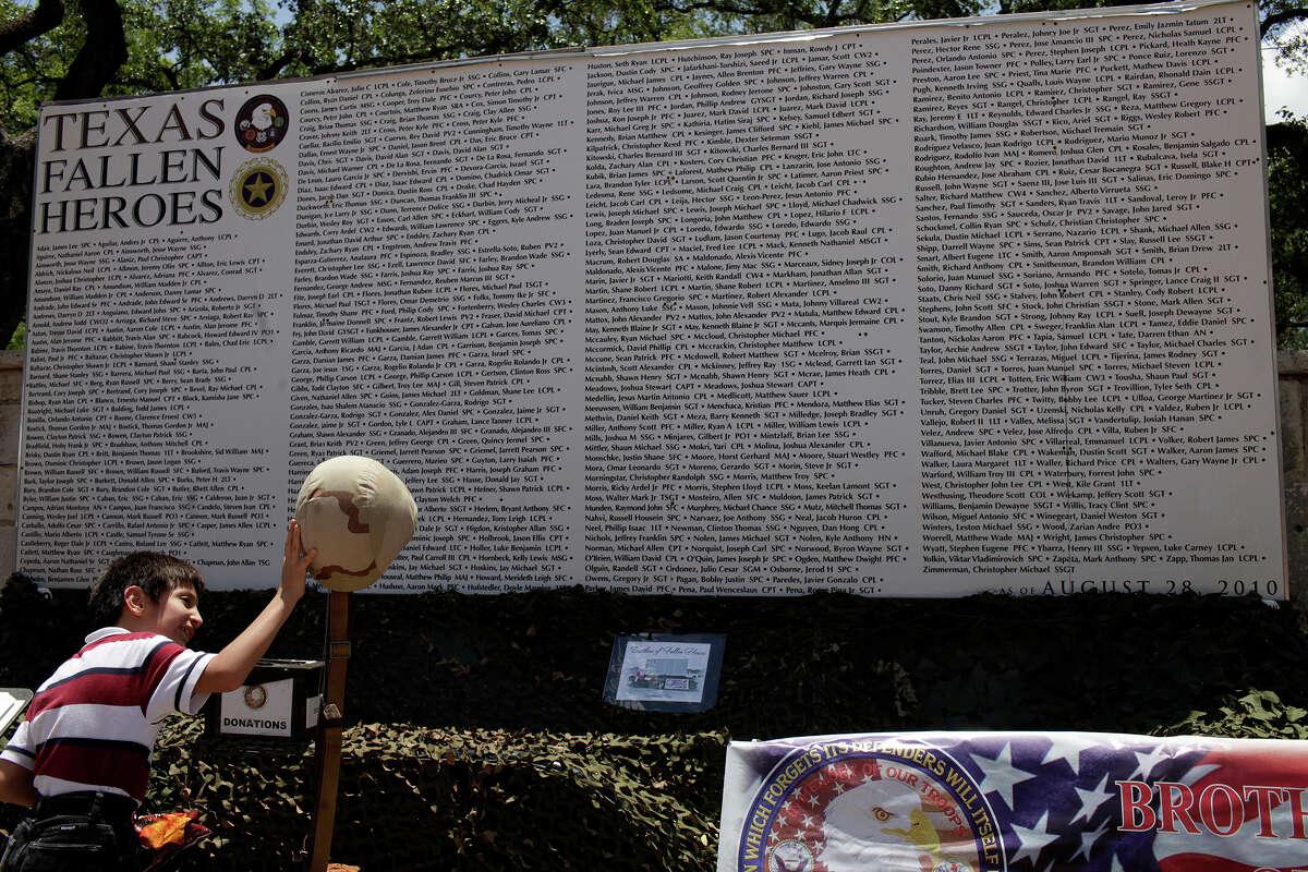 Angel Galindo, 8, of Laredo, looks at the Brothers of Fallen Heroes' Texas Fallen Heroes Memorial Wall display at La Villita in San Antonio on Saturday, May 19, 2012.