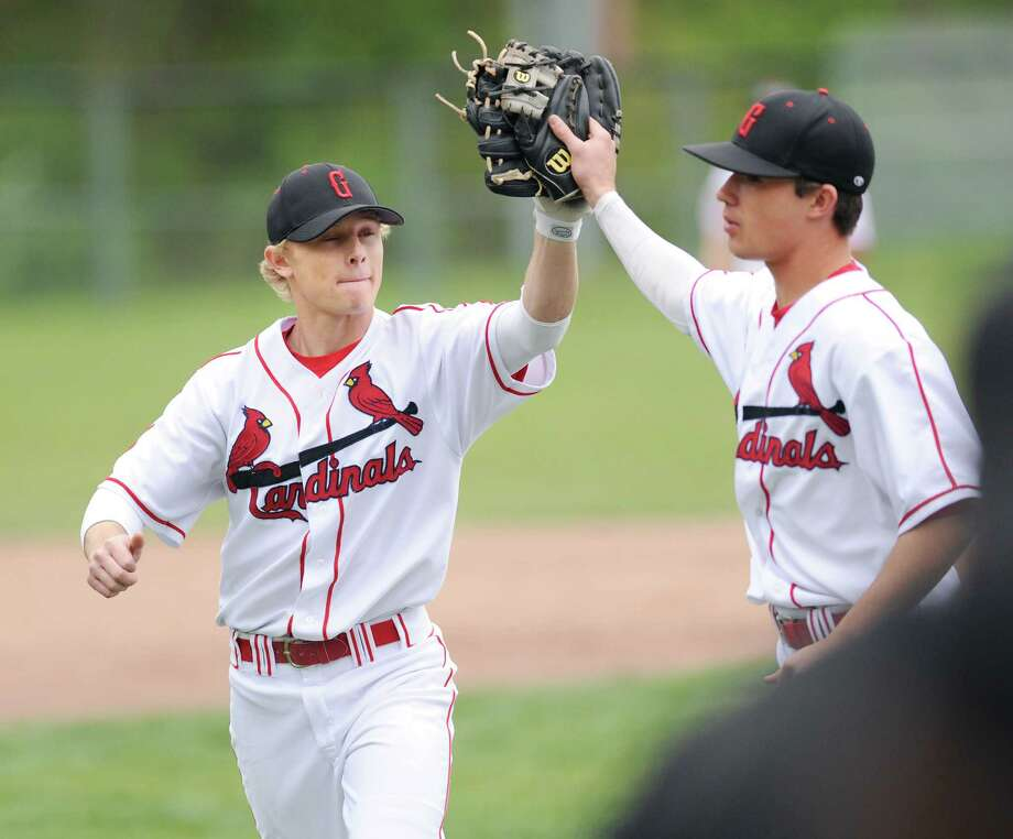 Second baseman Max Pruner, left, of Greenwich, high-fives teammate Dylan Callahan following a 4-0 win over McMahon. The undefeated Cardinals are the top seed in the FCIAC tournament. Photo: Bob Luckey / Greenwich Time