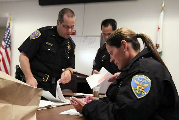 Officer Kim LaSalle, right, checks her messages following a weekly homeless meeting lead by Lieutenant Bill Roualdes, left, that addresses a verity of social programs designed to help the beat officer locate shelter for the needy Wednesday, May 16, 2012, in San Francisco, Calif. Photo: Lance Iversen, The Chronicle