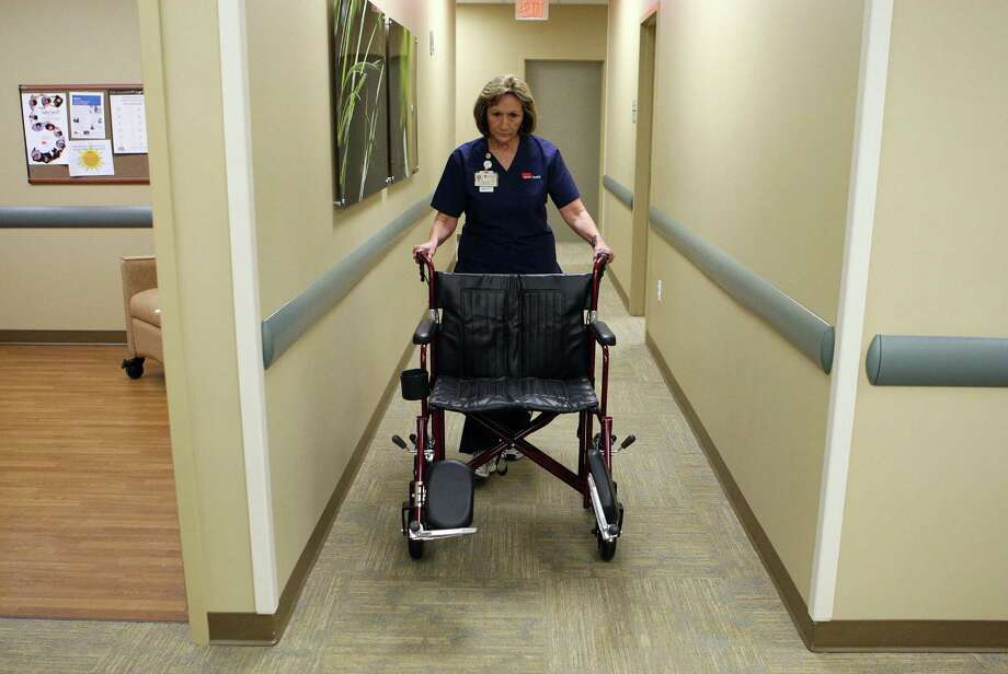 LVN Tina Layne demonstrates a wider wheelchair at the UTMB Multispecialty Center and Stark Diabetes Clinic in League City. Photo: James Nielsen / © Houston Chronicle 2012
