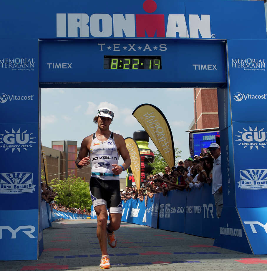 Justin Daerr crosses the finish line to place second in the Memorial Hermann Ironman Texas triathlon Saturday, May 19, 2012, in The Woodlands. Photo: James Nielsen, Chronicle / © Houston Chronicle 2012