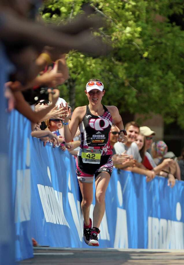 Caitlin Snow celebrates with the crown before crossing the finish line to place second in the women's division of the Memorial Hermann Ironman Texas triathlon Saturday, May 19, 2012, in The Woodlands. Photo: James Nielsen, Chronicle / © Houston Chronicle 2012