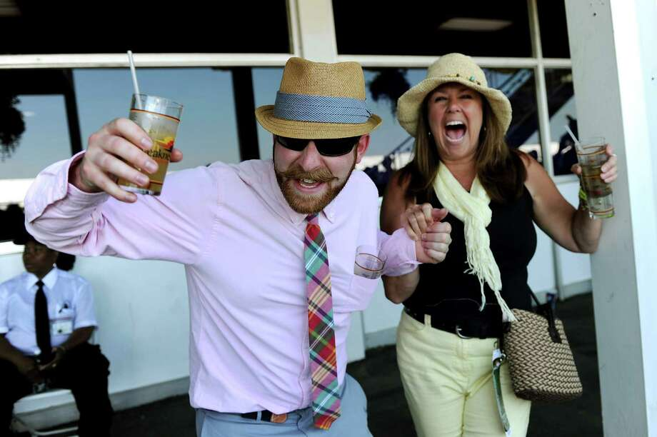 Joshua Rathbone and Monica McDowell of West Chester, Pennsylvania, cheer for a race prior to the 137th running of the Preakness Stakes at Pimlico Race Course on May 19, 2012 in Baltimore, Maryland. Photo: Patrick Smith, Getty Images / 2012 Getty Images