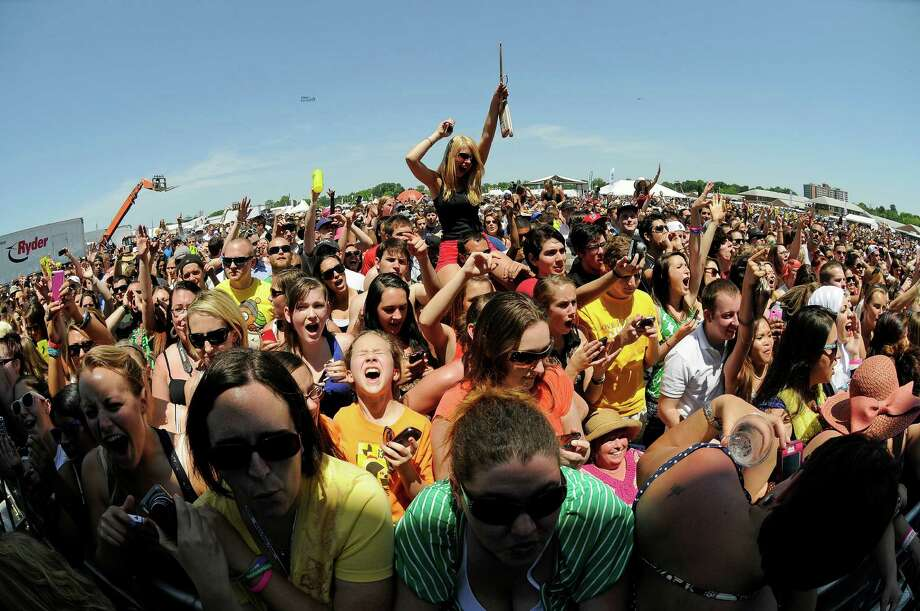 In this image taken with a fisheye lens, fans react as they watch Wiz Khalifa perform in the infield before the 137th Preakness Stakes horse race at Pimlico Race Course, Saturday, May 19, 2012, in Baltimore. Photo: Nick Wass, Associated Press / FR67404 AP