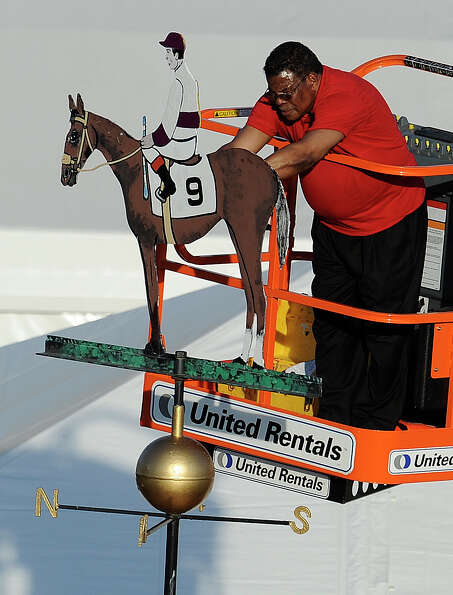 A worker paints the colors of the silks worn by jockey Mario Guiterrez on a weather vane after ridin
