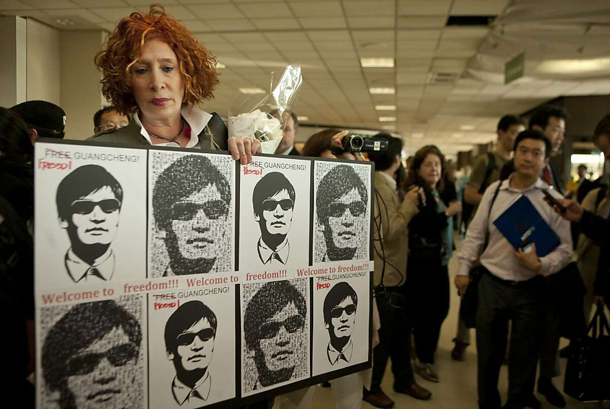 NEWARK, NJ - MAY 19: Diane Gatterdam holds a sign with images of blind Chinese activist Chen Guangcheng as she waits for him to arrive in the United States at Newark Liberty Airport May 19, 2012 in Newark, New Jersey. China allowed the activist to leave a hospital in Beijing and board a plane for the U.S., a move that could signal the end of a diplomatic standoff between the two countries. (Photo by Lee Celano/Getty Images)