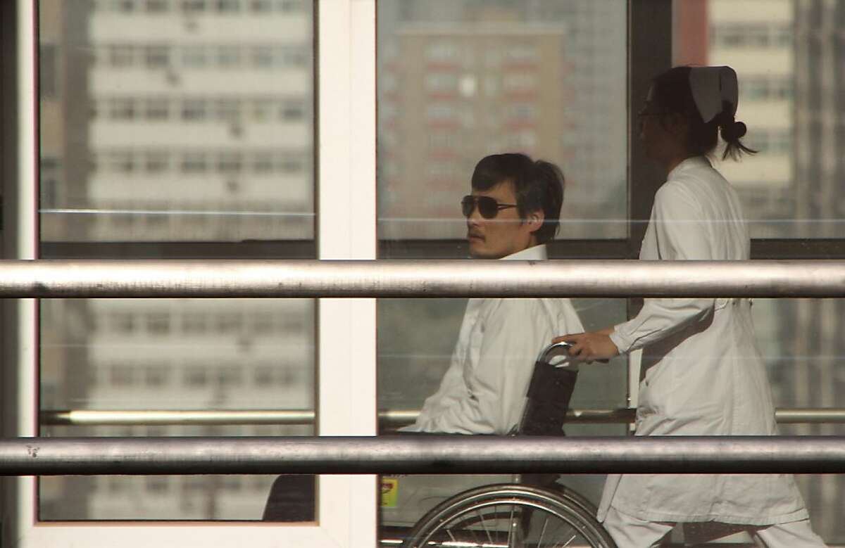 (FILES) In a file picture taken on May 2, 2012, Chinese activist activist Chen Guangcheng (L) is seen in a wheelchair pushed by a nurse at the Chaoyang hospital in Beijing on May 2, 2012. Blind Chinese activist Chen Guangcheng said on May 19, 2012 he was at a Beijing airport with his family and believed he would be flying to New York, signalling an end to the month-long saga was close. AFP PHOTO/Jordan Pouille/FILESJordan Pouille/AFP/GettyImages