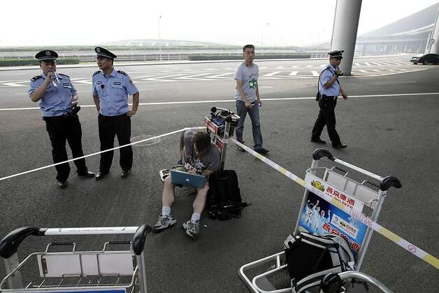 Chinese police officers and a plain clothes security person watch over a media cordon set up outside the VIP terminal of the Capital Airport during a stake out for the blind activist Chen Guangcheng in Beijing Saturday, May 19, 2012. Chen was hurriedly taken from a hospital Saturday and boarded a plane that took off for the United States, closing a nearly monthlong diplomatic tussle that had tested U.S.-China relations. (AP Photo/Ng Han Guan) Photo: Ng Han Guan, Associated Press