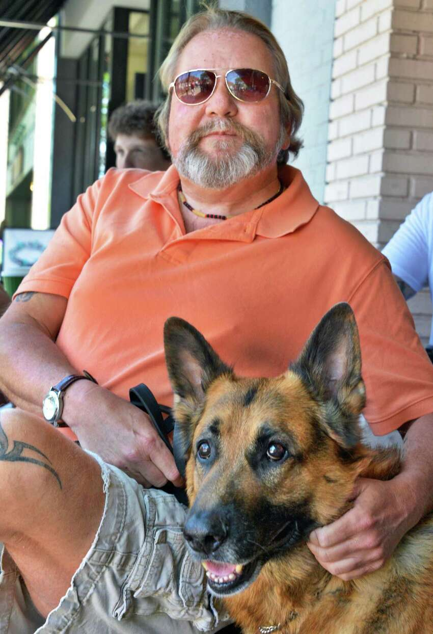 John Tighe of Milton, and his dog Bruno sit at a sidewalk cafe in Saratoga Springs Friday, May 18, 2012. Tighe was mistakenly dropped by his health insurance company in a mixup. The insurer is working to fix the problem, but meanwhile a needed CT scan is delayed. (John Carl D'Annibale / Times Union)