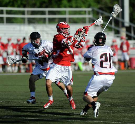 New Canaan's Teddy Bossiy, left, and Jack Bratches, right, defend Greenwich's Kyle Foote during Saturday's FCIAC boys lacrosse quarterfinal game at New Canaan High School on May 19, 2012. Photo: Lindsay Niegelberg / Stamford Advocate