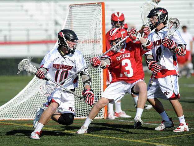 New Canaan's Peter Kraus carries the ball as he is defended by Greenwich's Jack Nail during Saturday's FCIAC boys lacrosse quarterfinal game at New Canaan High School on May 19, 2012. Photo: Lindsay Niegelberg / Stamford Advocate